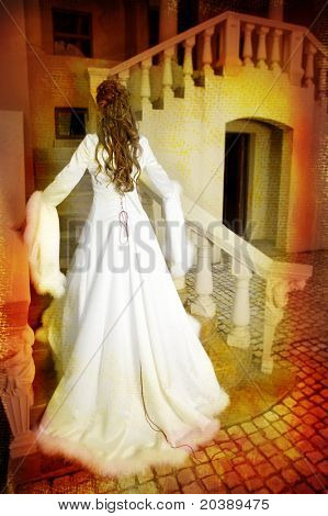 beautiful bride with long brown hair in a long silk white coat with wide sleeves and feather trimming walking up tuscan style staircase