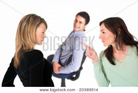 Neatly dressed brunette pointing accusing finger at a blond woman with a smiling man on a chair in the background