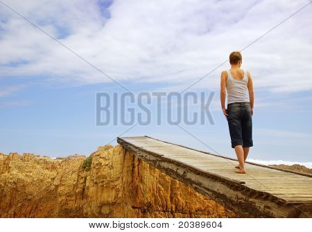 Young woman on old wooden bridge over rocky gorge â?? view from the back, copy-space over sky