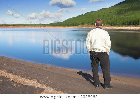 Young man on the lake shore with forest and clouds reflecting in the water. ISO 100, no sharpening