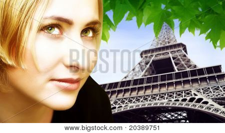 Beautiful blond woman on Eiffel Tower in summer background. Tower is in soft focus.