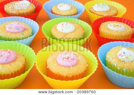 Display of small party cakes with icing sugar in bright plastic cups. Focus on middle cake