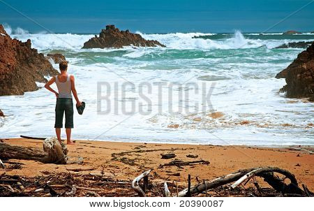 Stormy ocean view with a woman standing on the sand beach, evening in Knysna, South Africa