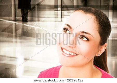 Young brunette smiling woman with large brown eyes on grunge office background