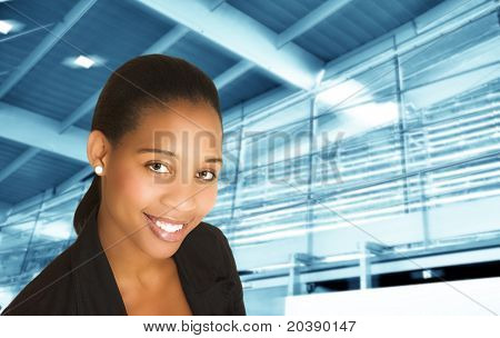 Smiling African businesswoman in black suit on futuristic abstract architecture background