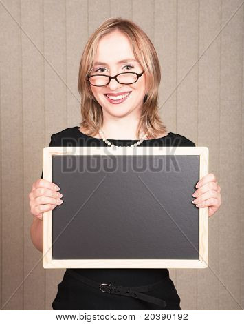Young smiling blond woman teacher in black dress and pearls, wearing glasses with empty blackboard