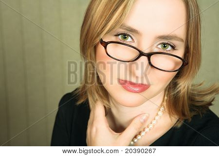 Young blond business woman with pearl necklace and green eyes looking with tired green eyes over her glasses