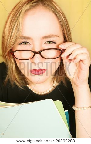 Blond businesswoman in black with pearls squinting over brown glasses in doubt, holding files