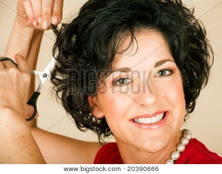 Beautiful happy adult woman  with black curly hair cutting her hair with scissors. Visible skin texture with pores and wrinkles