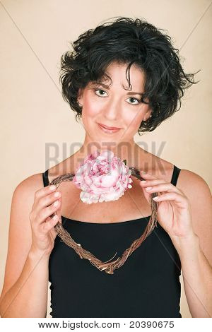 Beautiful happy adult woman  with black curly hair and soft natural make-up, holding a twig heart wreath with pink peony