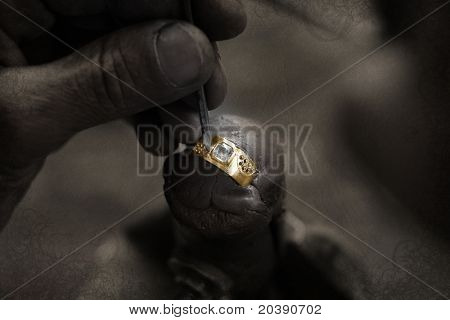 Goldsmith working on an unfinished 22 carat gold ring with big diamond with his hard working hands on grunge paper background