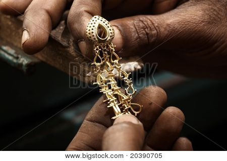Goldsmith holding an unfinished 22 carat gold earring in his hard working hands and fine gold dust on the hands. Shallow DOF - focus on the earring top