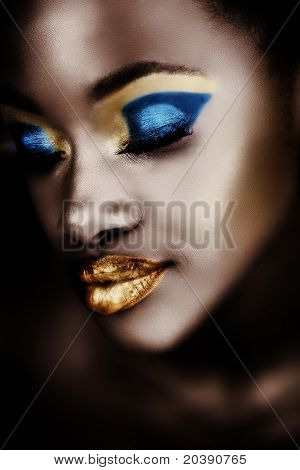 African woman with gold and blue metallic make-up and full shiny lips