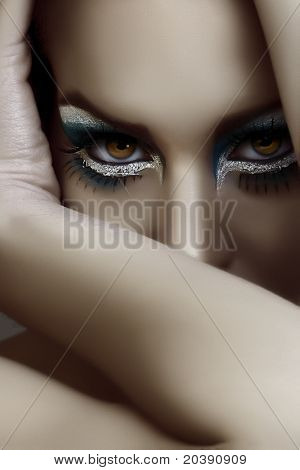 beautiful woman with dark goth make-up covering her face with an arm