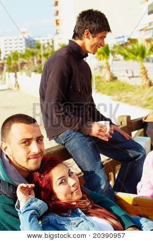 young couple enjoying time in an outdoor coffee shop with friends