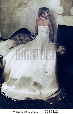 beautiful blond bride in long wedding dress resting on grunge vintage background with stains and spots