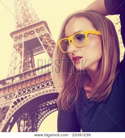 beautiful young blond woman wearing fashionable yellow glasses against Eiffel Tower in Paris with cross-processed effect.