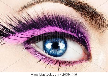 Macro of woman's eye with long pink feather fake eyelashes.
