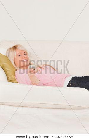 Gut aussehende blonde Frau posiert beim liegen auf dem Sofa im Wohnzimmer