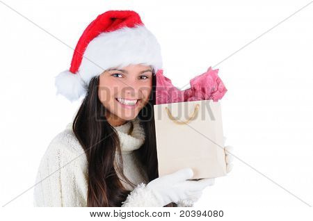 Smiling young woman wearing a Santa Claus hat holding a small Christmas gift bag up to her face. Horizontal format isolated on white.