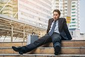 Desperate Businessman Sitting Hopelessly On Stair Floor poster