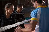 Volleyball players giving handshake through net at court poster
