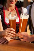 Couple in traditional Bavarian Tracht - Dirndl and Lederhosen - in a beer tent at the Oktoberfest or