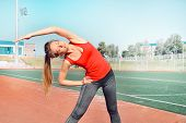 A Pretty Woman Athlete Stretching Her Body At Stadium Track poster