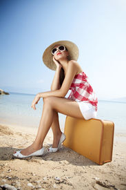 picture of summer beach  - young female styled in 50s summer outfit sitting on a retro suitcase on the beach - JPG
