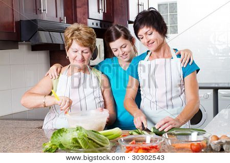 teen girl watching mother and grandmother cooking in kitchen
