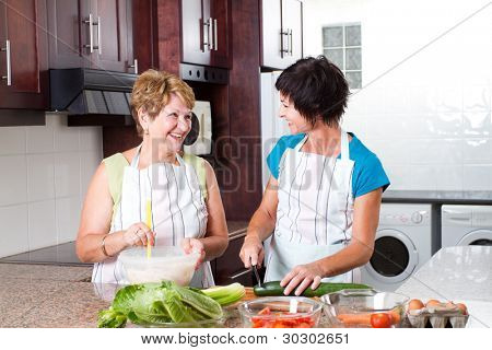 happy senior mother and middle aged daughter cooking in kitchen