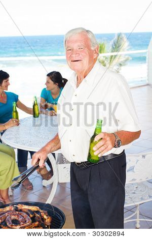 happy grandpa doing barbeque for the family in background