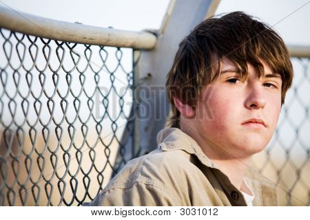 Teen Portrait Against Fence