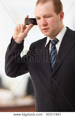 young businessman speaking mobile phone in office