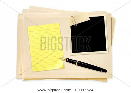 Stack of manila file folders, with blank vintage photo paperclipped, with yellow notepaper and fountain pen.