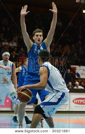 KAPOSVAR, HUNGARY – FEBRUARY 18: Kornel Kiss (with ball) in action at a Hungarian Championship basketball game with Kaposvar (white) vs. Fehervar (blue) on February 18, 2012 in Kaposvar, Hungary.