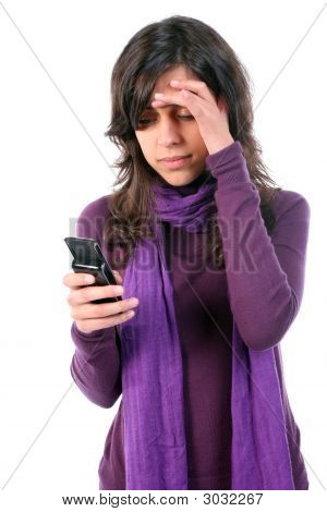 Young Girl Tired And With Headache, Reading A Sms On Her Cellphone