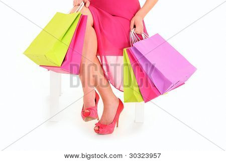 A picture of a young woman sitting with shopping bags over white background