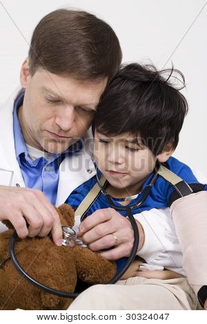 Doctor playing with little boy in hospital