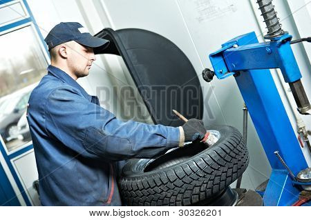 serviceman repairman worker lubricating car tyre at workshop befor fitting