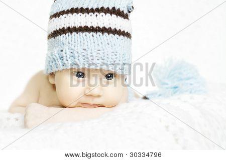 Newborn Baby Closeup Portrait In Blue Woolen Hat. Indigo Eyes