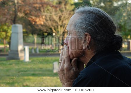 Man Sitting At Gravesite