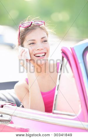 Vintage woman in retro car talking on mobile smart phone. Beautiful young mixed race woman driving in pink car smiling happy.