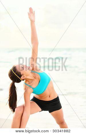 Mujer de estiramiento de yoga en la playa. Serena deportiva mujer haciendo yoga plantea durante al aire libre. Hermosa feliz