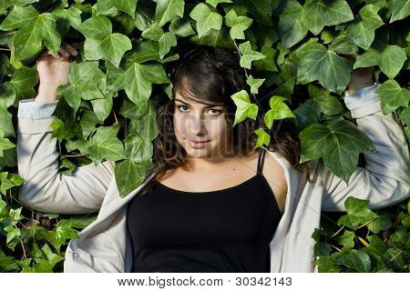 Beautiful Girl Surrounded By Green Leaves