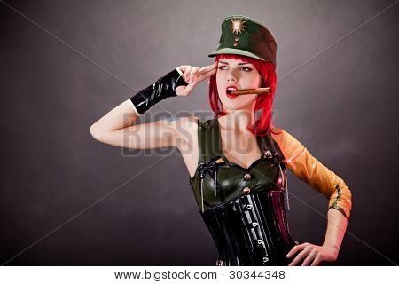 Young redhead woman dressed in military style latex and green cap, studio shot