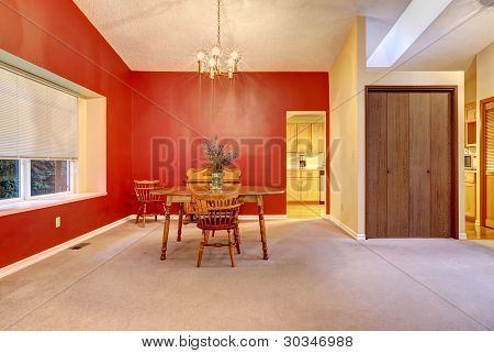Large Dining Room With Red Wall And Small Wood Table.