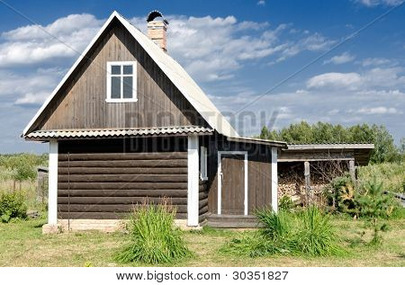 Wooden country house in a green field
