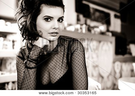 Charming sexy  woman in black clothes  sits at magnificent cafe  restaurant.