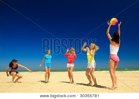 Gruppe der fröhliche Mädchen spielen Volleyball, übergeben den Ball einander am Strand